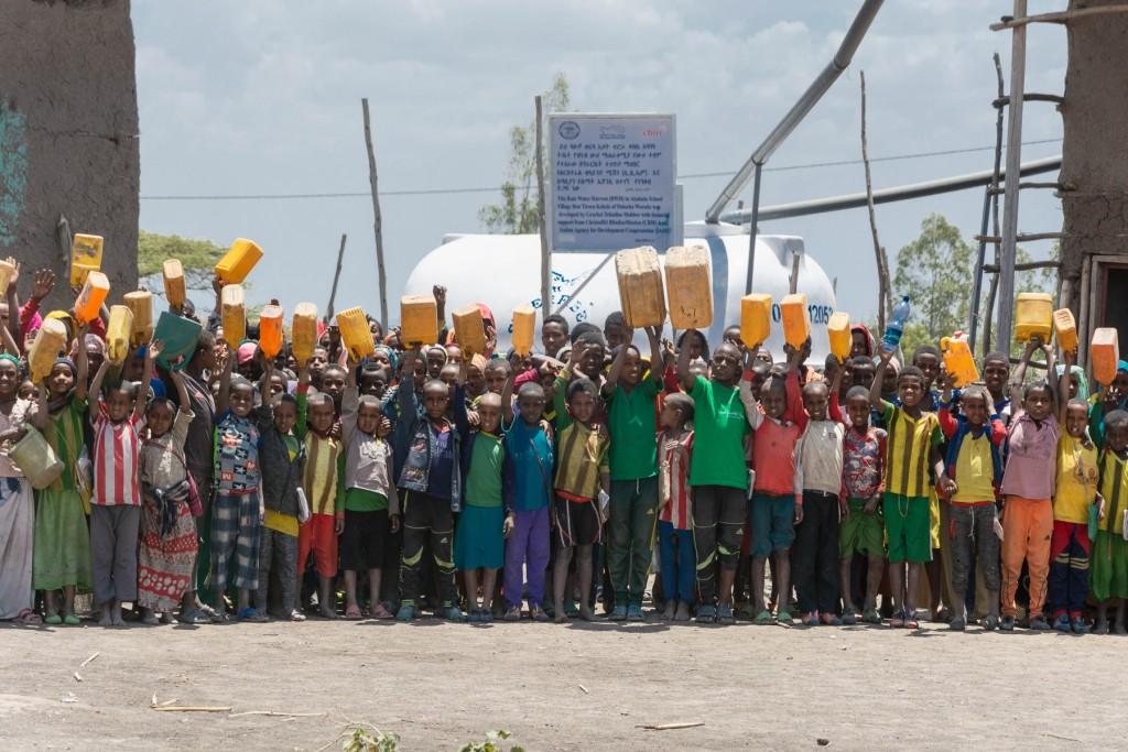gruppo di bambini con taniche gialle per l'acqua