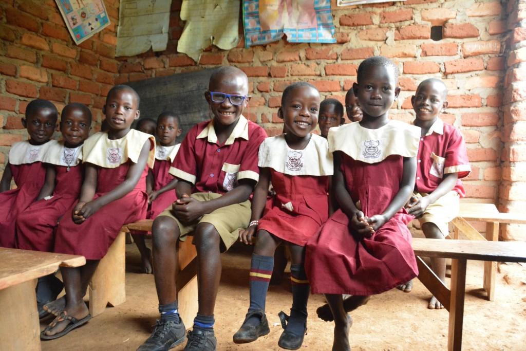 Mathias con gli occhiali da vista seduto a scuola tra i compagni
